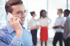 Бизнесмен говоря на мобильном телефоне при коллеги обсуждая в предпосылке Стоковые Фотографии RF