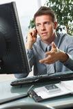 Бизнесмен говоря на телефоне в офисе стоковое изображение