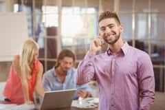 Бизнесмен говоря на телефоне в офисе с работой коллег Стоковые Фотографии RF