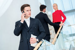 Бизнесмен говоря на телефоне Молодой бизнесмен стоя дальше Стоковая Фотография RF