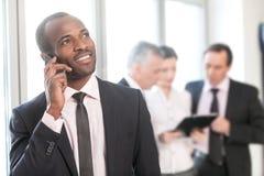 Бизнесмен говоря на умном телефоне с коллегами в backgr Стоковая Фотография RF