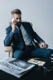 Бизнесмен говоря на smartphone на сером цвете Стоковая Фотография RF