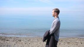 Бизнесмен гуляет вдоль пляжа в костюме восхищает красивый пляж видеоматериал