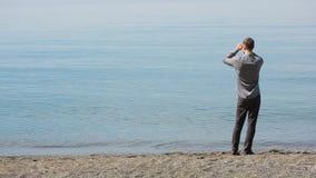 Бизнесмен гуляет вдоль пляжа в костюме, восхищает красивый пляж акции видеоматериалы