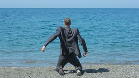 Бизнесмен гуляет вдоль пляжа в костюме, восхищает красивый пляж видеоматериал