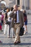 Бизнесмен гуляя и говоря на телефоне Стоковое фото RF