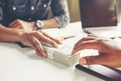 Бизнесмен давая деньги к его партнеру пока делающ контракт - стоковое изображение