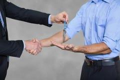 Бизнесмен давая ключи и тряся руки Стоковые Изображения
