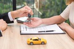 Бизнесмен давая ключ автомобиля над документом wi применения автокредита стоковые фотографии rf