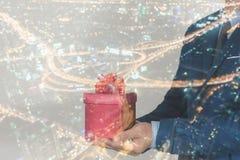 Бизнесмен давая подарок к партнеру с backg города ночи современным Стоковая Фотография