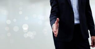 Бизнесмен давая руку против предпосылки запачканной белизной Стоковое Фото