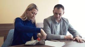 Бизнесмен дает деньги женщины, она кладет его в пластиковый конверт сток-видео