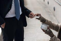 Бизнесмен дает деньги к попрошайке Стоковая Фотография