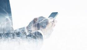 Бизнесмен двойной экспозиции используя мобильный умный телефон, и технология сетевого подключения в городе Сеть дела, blockchain стоковое изображение