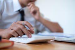 Бизнесмен делая вычисление с ручкой в руке, концепции финансов стоковая фотография rf