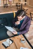 Бизнесмен делая обработку документов в кафе Стоковая Фотография RF