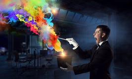 Бизнесмен демонстрируя волшебство Мультимедиа стоковое изображение rf