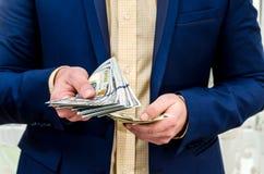Бизнесмен держа большое количество доллара Стоковая Фотография RF