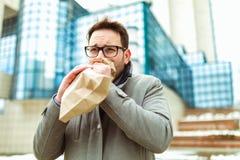 Бизнесмен держа бумажную сумку над ртом если имеющ приступ паники стоковая фотография