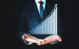 Бизнесмен держа диаграмму дела финансы яичка диетпитания принципиальной схемы предпосылки золотистые стоковые изображения rf