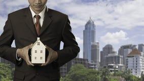 Бизнесмен держа домашнюю модель Стоковая Фотография