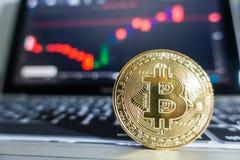 Бизнесмен держа золотое Bitcoin перед компьтер-книжкой с запасом Стоковая Фотография RF