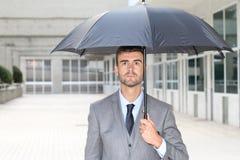 Бизнесмен держа зонтик изолированный в размерах офиса стоковые изображения rf