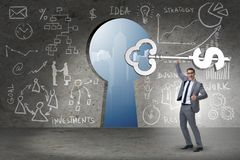 Бизнесмен держа ключевым к финансовым успеху и процветанию Стоковые Фото