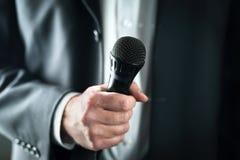 Бизнесмен держа микрофон Речь публичного выступления и давать в костюме для концепции аудитории стоковые изображения rf