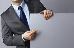 Бизнесмен держа пустую доску стоя на серой предпосылке Стоковая Фотография RF