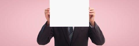 Бизнесмен держа пустую карточку против розовой предпосылки Стоковое Изображение RF