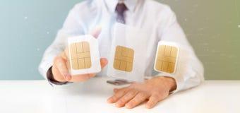 Бизнесмен держа различный размер карточки 3d r sim smartphone Стоковые Изображения