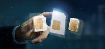Бизнесмен держа различный размер карточки 3d r sim smartphone Стоковое фото RF