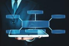 Бизнесмен держа цифровой планшет со схемой технологического процесса владение домашнего ключа принципиальной схемы дела золотисто стоковая фотография rf