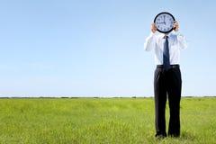 Бизнесмен держа часы на лужке Стоковые Фотографии RF