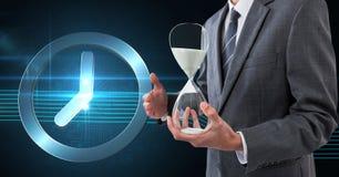Бизнесмен держа часы песка против предпосылки с часами Стоковое Изображение