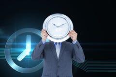 Бизнесмен держа часы против предпосылки с часами Стоковые Изображения
