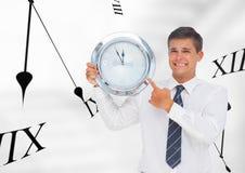 Бизнесмен держа часы против предпосылки с часами Стоковое Фото