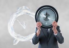 Бизнесмен держа часы против предпосылки с часами Стоковое Изображение RF