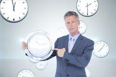 Бизнесмен держа часы против предпосылки с часами Стоковое фото RF