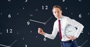 Бизнесмен держа часы против предпосылки с часами Стоковое Изображение