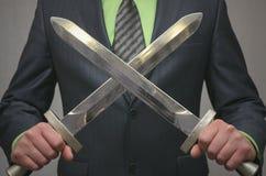 Бизнесмен держит в руке пересеченное оружие шпаги игрушки Концепция агента безопасности Стоковая Фотография RF