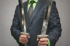 Бизнесмен держит в руке пересеченное оружие шпаги игрушки Концепция агента безопасности Стоковая Фотография