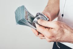 Бизнесмен держит деньги в его руках и отсчетах его доход Деньги штабелированы в долларовых банкнотах стоковая фотография rf
