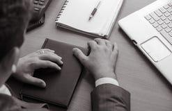 Бизнесмен держит его руки на закрытой тетради Стоковые Фото