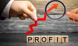 """Бизнесмен держит красную поднимающую вверх стрелку и надпись """"выгоду """" Концепция успеха в бизнесе, финансового роста и богатства  стоковое фото rf"""