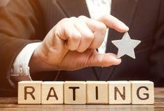 Бизнесмен держит одну звезду над деревянными блоками с оценкой слова Концепция отрицательного результата воздействия Низкое качес стоковые изображения rf