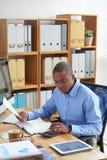 бизнесмен документирует финансовохозяйственную деятельность стоковая фотография