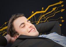 Бизнесмен лежа назад против желтого doodle диаграммы и серой предпосылки Стоковые Фото