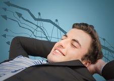 Бизнесмен лежа назад против doodle диаграммы и голубой предпосылки Стоковая Фотография